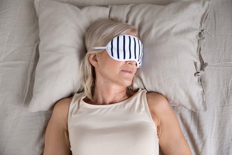 Calm old woman enjoying sleep wear sleeping mask in bed stock image