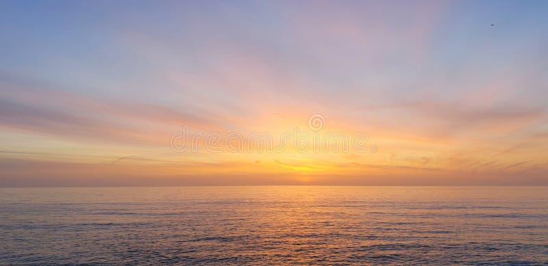 Calm pastel colored beach sea ocean sunset stock image