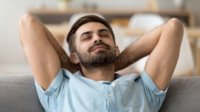 Calm peaceful man relaxing with closed eyes leaning back on sofa. Calm peaceful man relaxing with closed eyes leaning back on comfortable sofa, tired guy fall royalty free stock photography