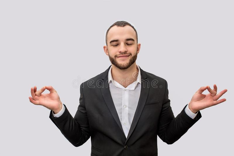 Calm and peaceful young man in suit meditating. He keeps eyes closed. His hands are aside of body. Isolated on white stock photography