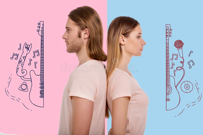 Calm people standing with their backs touching and thinking about music. Music fans. Young serious couple standing behind each other and looking thoughtful after stock photo