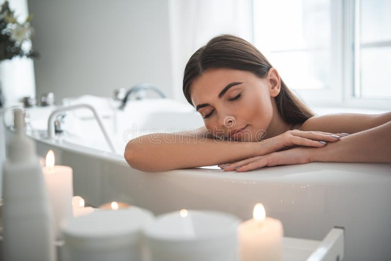 Calm pleased lady having relax in bathroom stock photos