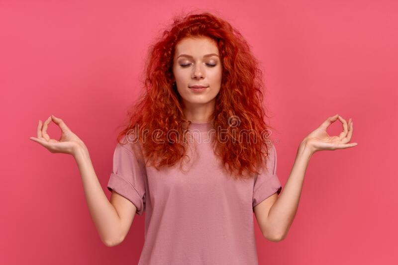Calm red haired woman relaxing meditation, no stress-free relief at work stock image