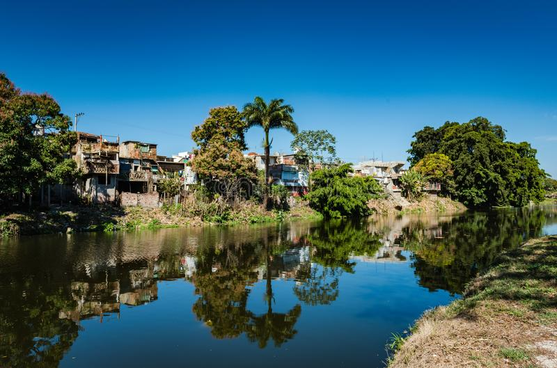Yayabo River Banks. Calm reflections on Yayabo River with view of apartment housing in Sancti Spiritus , Cuba stock photography