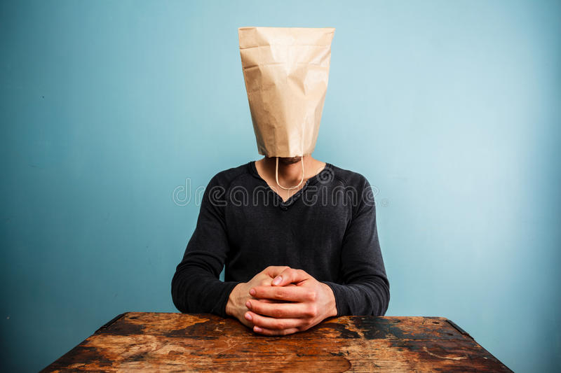 Calm and relaxed man with bag over head stock photography
