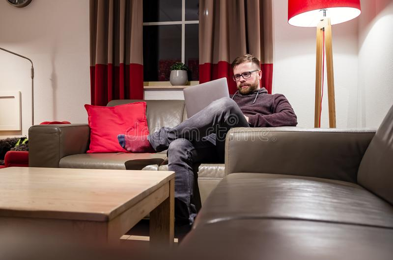 Man looks at his laptop, he reads messages or works, sitting in a comfortable position on a leather sofa, in a cozy home royalty free stock photo