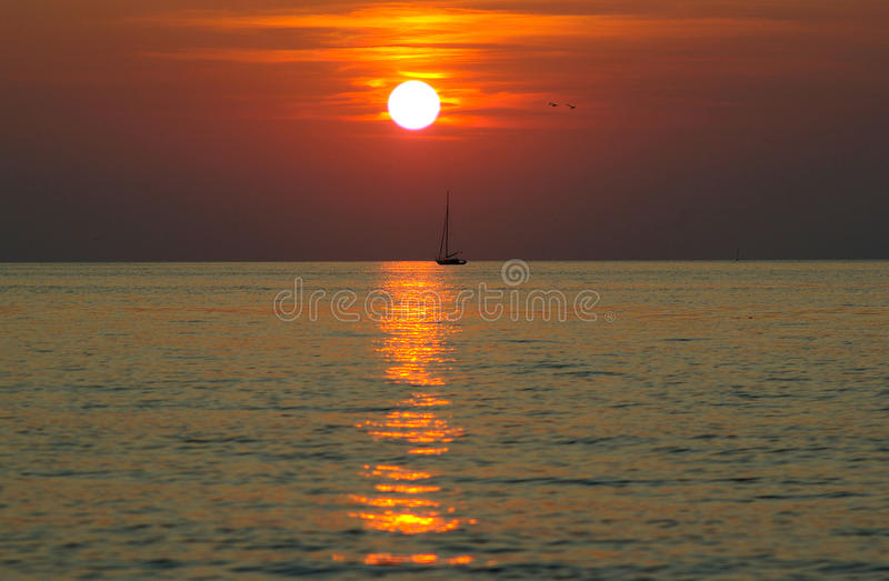 A calm on the sea. And a small yacht stock photography