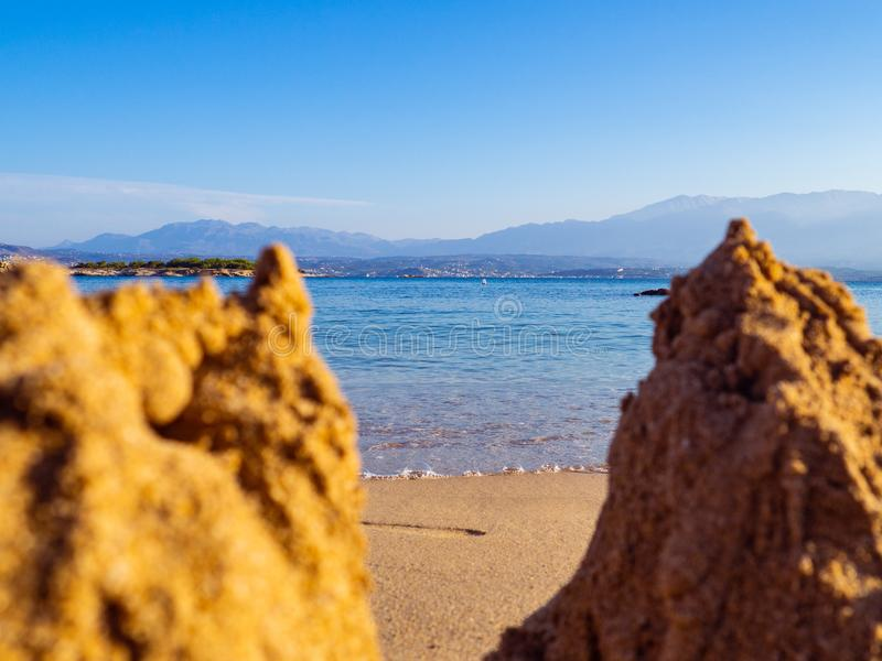 Calm sea and a empty beach - small sandcastles in the front royalty free stock photos