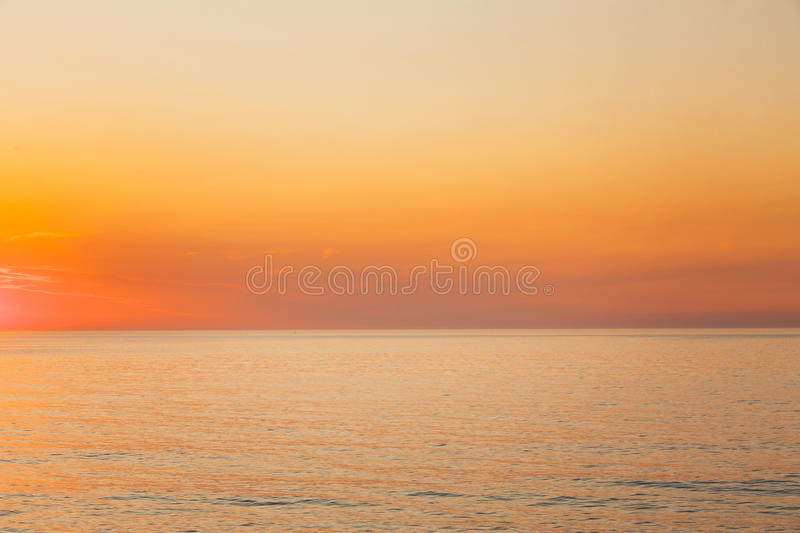 Calm Sea Or Ocean And Yellow Clear Sunset Or Sunrise Sky Background. Warm Colors royalty free stock photo