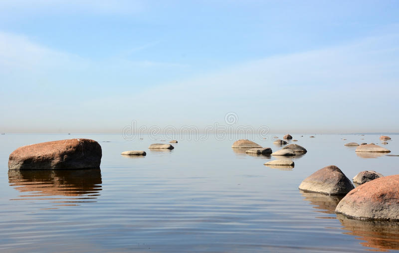 Calm sea. With stones and blue sky background stock image