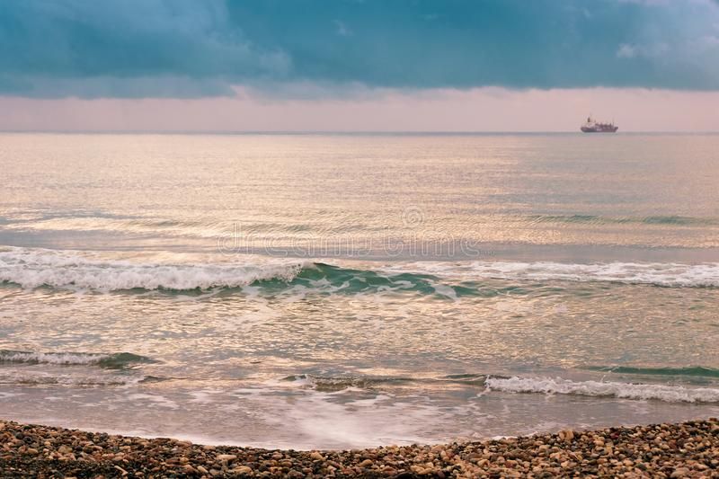 Calm sea waves against a dark and stormy sky stock photos
