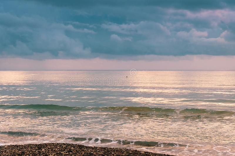 Calm sea waves against a dark and stormy sky stock image