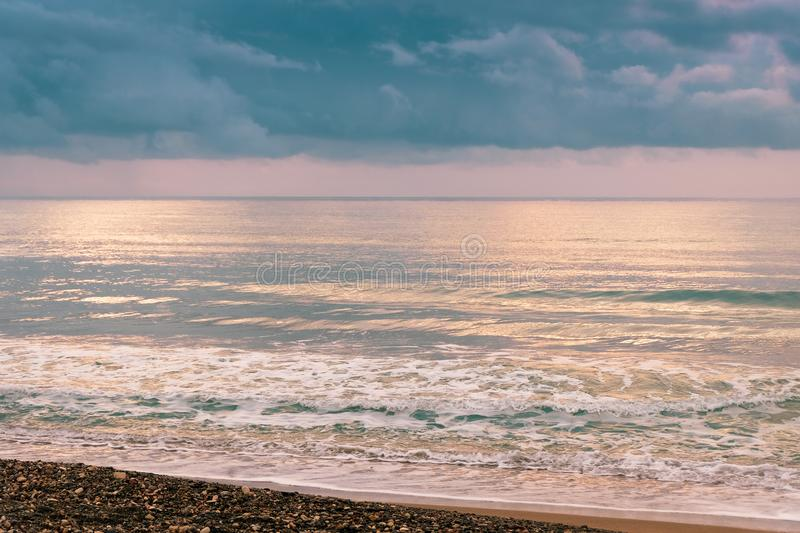 Calm sea waves against a dark and stormy sky stock photo