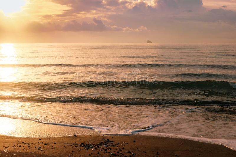 Calm sea waves in golden light in Larnaca stock images
