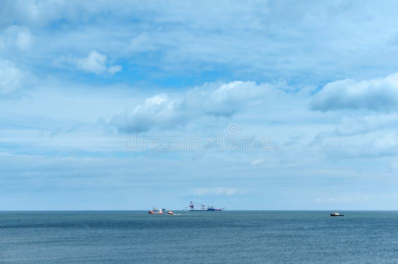 Calm sea without waves and blue sky, oil and gas drilling rig in the distance to the sea royalty free stock photos