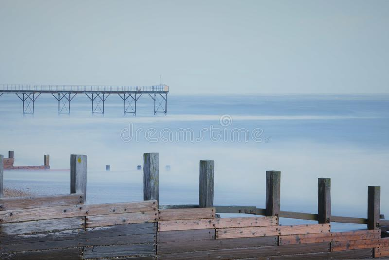 Long exposure photography image sea pier in Bognor Regis taken South coast England UK. Calm seas using long exposure photography of beach sea groynes and pier at royalty free stock image