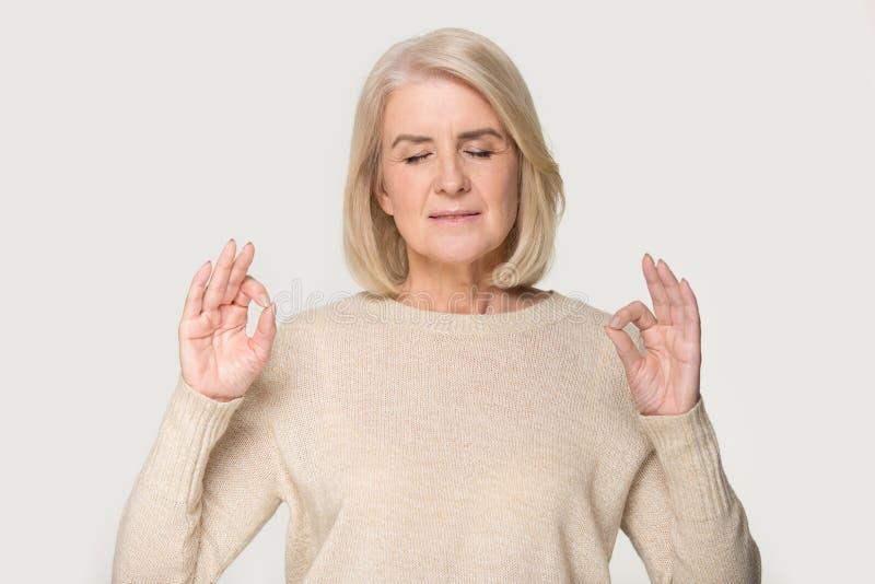 Calm senior woman isolated on studio background meditating. Peaceful senior woman isolated on grey studio background stand meditating with mudra hands, calm stock photos