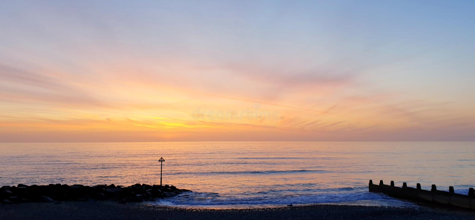 Calm pastel colored beach sea ocean sunset royalty free stock images
