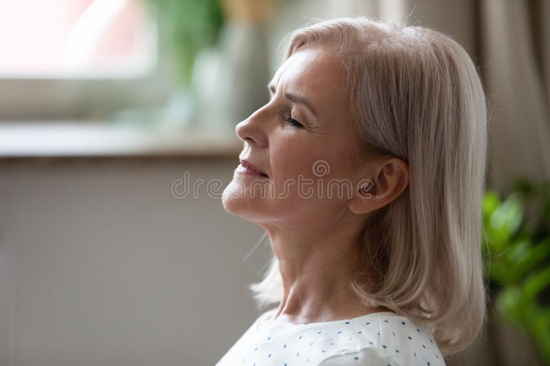 Calm serene middle aged woman breathing with eyes closed royalty free stock photo