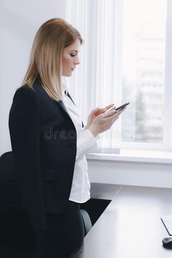 Calm serious young attractive blonde uses phone near table in office royalty free stock image