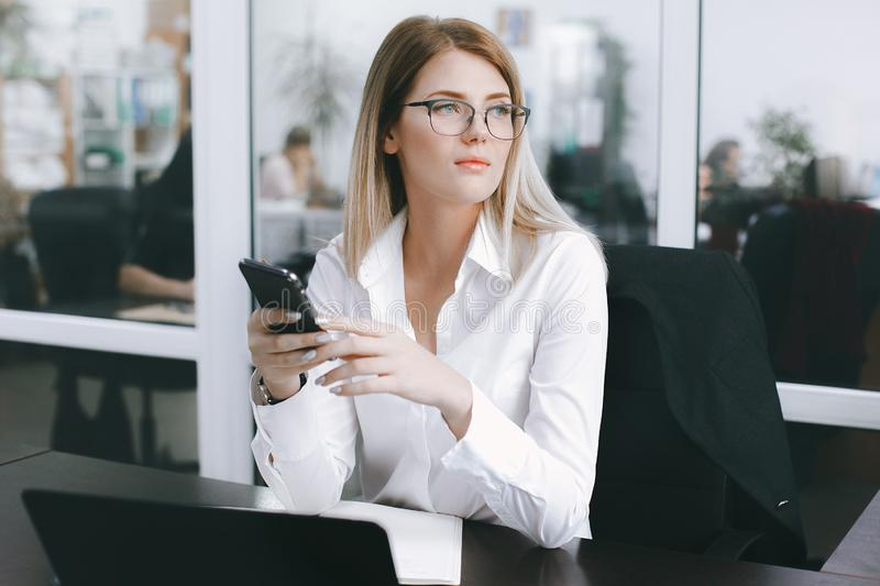 Calm serious young attractive blonde uses phone while working at table in office royalty free stock photo