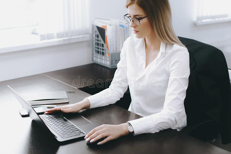 Calm serious young attractive blonde woman uses laptop to work at table in office royalty free stock image