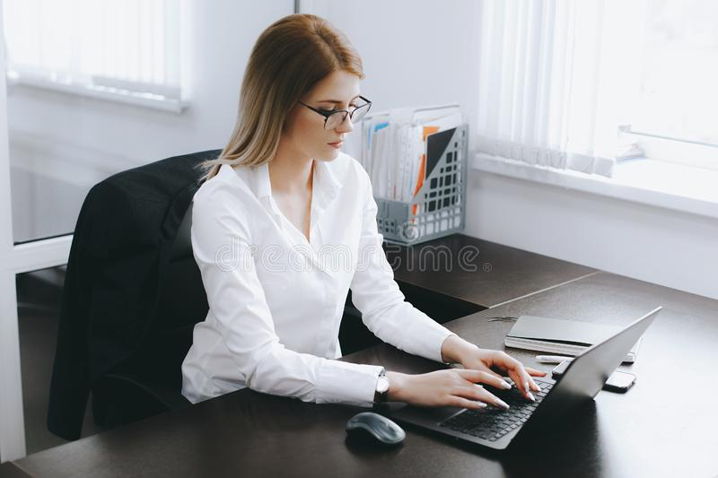 Calm serious young attractive blonde woman uses laptop to work at table in office stock photography