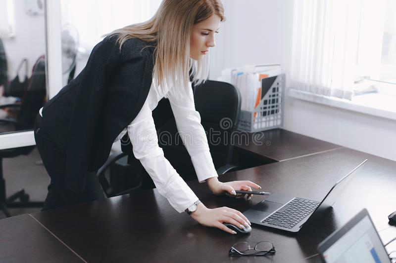 Calm serious young attractive blonde woman uses laptop to work at table in office stock images