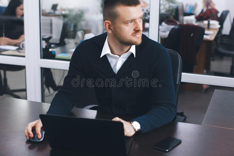 Calm serious young man uses laptop to work at table in office stock photo