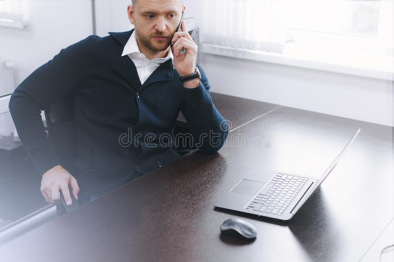 Calm serious young man uses phone while working at table in office stock image