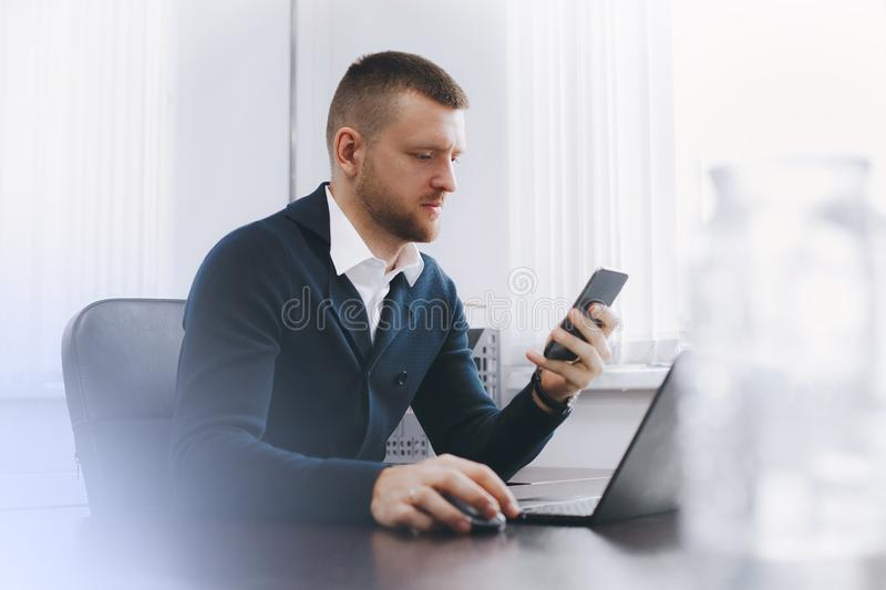 Calm serious young man uses phone while working at table in office stock photos