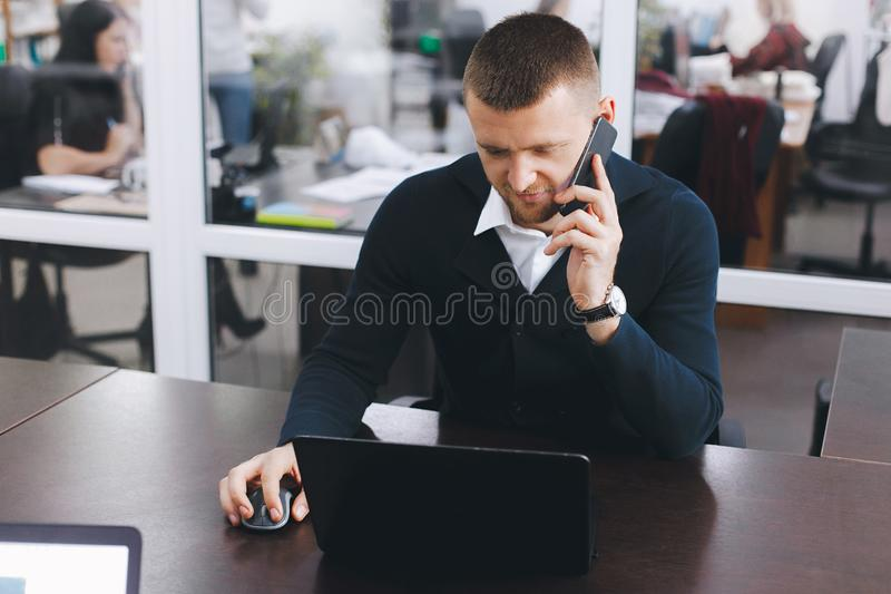 Calm serious young man uses phone while working at table in office royalty free stock photos