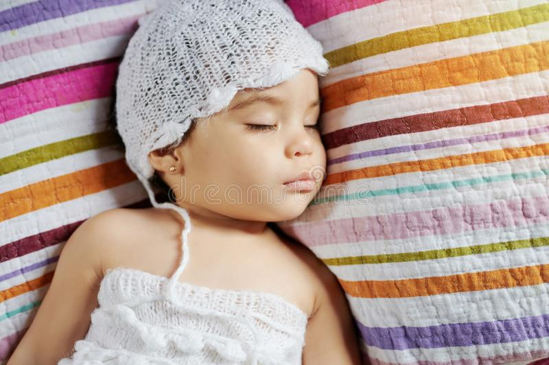 Calm sleeping baby girl. Above top view on colorful background stock image