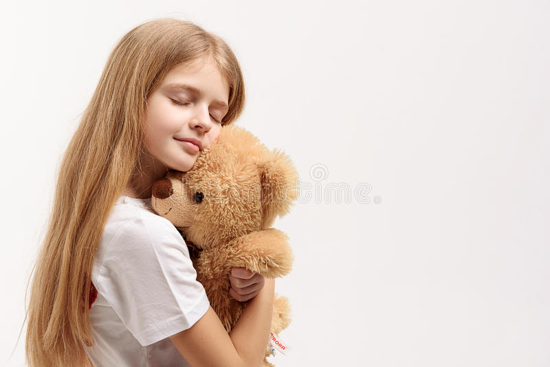 Calm small female kid keeping toy. Little girl is hugging toylike bear and standing with closed eyes. Portrait. Isolated. Copy space on right side royalty free stock images