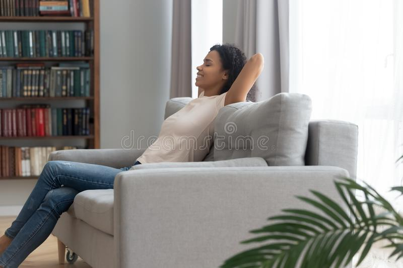 Calm smiling African American woman relaxing on couch at home stock image
