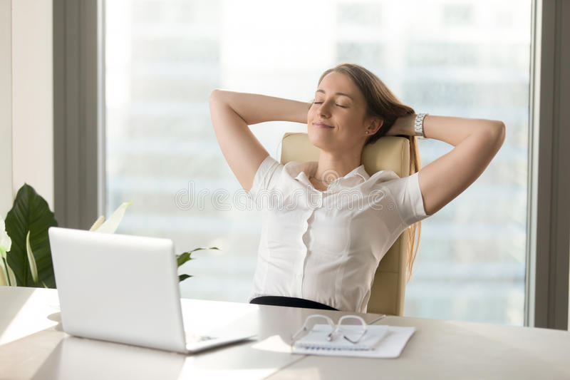 Calm smiling businesswoman relaxing at comfortable chair hands b. Calm smiling businesswoman relaxing at comfortable office chair hands behind head, happy woman royalty free stock photos