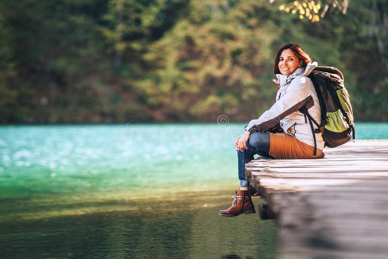 Calm smiling woman traveler sits on wood bridge near the mountain lake at sunny autumn day royalty free stock photos