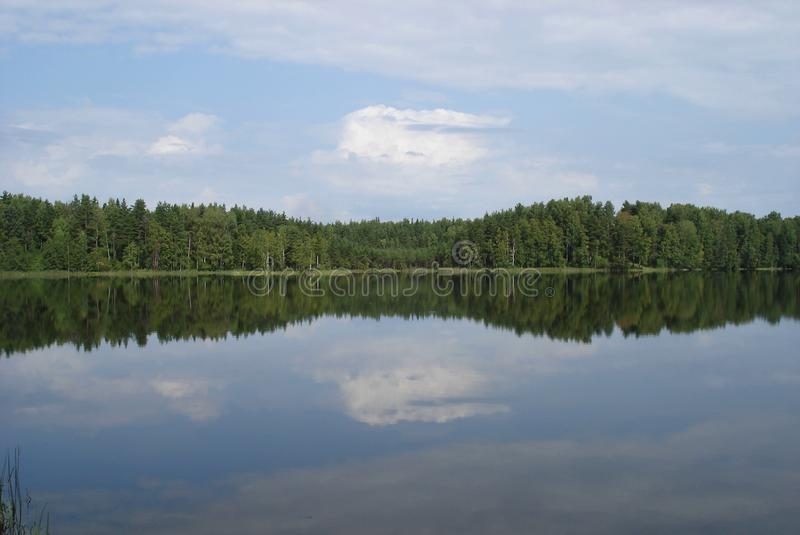 Reflection of clouds on the smooth surface of the lake royalty free stock photo