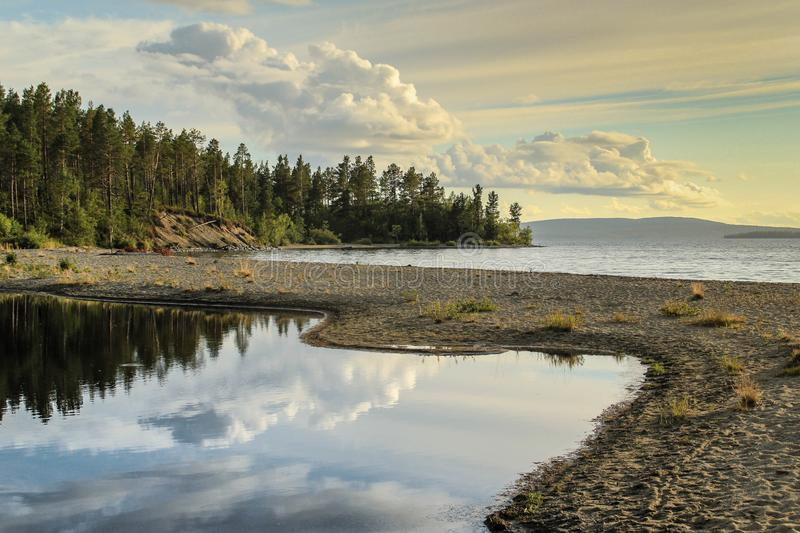 The calm and smooth water of the lake in which the forest and clouds are reflected. stock photo