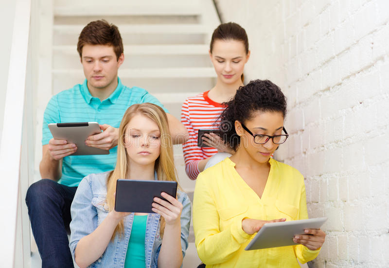 Calm students with tablet pc computer. Education and technology concept - calm students with tablet pc computer sitting on staircase royalty free stock photos