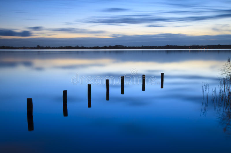 Download Calm Sunrise Over A Lake With Clouds Reflection In Royalty Free Stock Image - Image: 12040946