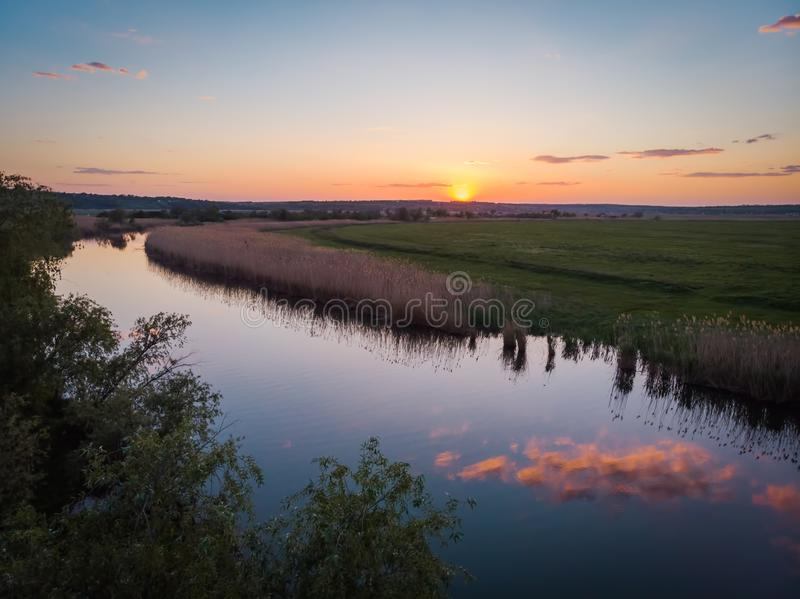 The calm surface of the river and the reflections of clouds, orange sunset, green fields and meadows in a quiet warm summer evenin royalty free stock photo