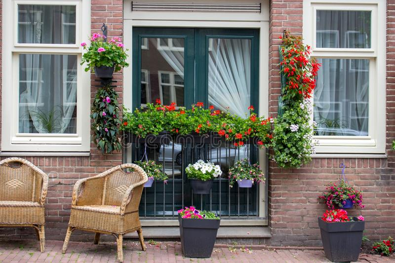 Calm terrace with chairs and flower pots. Exterior of unknown brick building in Amsterdam, Netherlands. Entrance with flowers. Calm terrace with chairs and stock photography