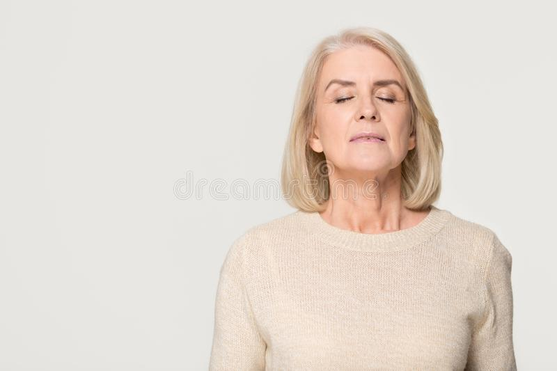 Calm mid aged woman breathing fresh air isolated on background. Calm tranquil mid aged old woman meditating breathing fresh air, serene mindful mature senior royalty free stock images