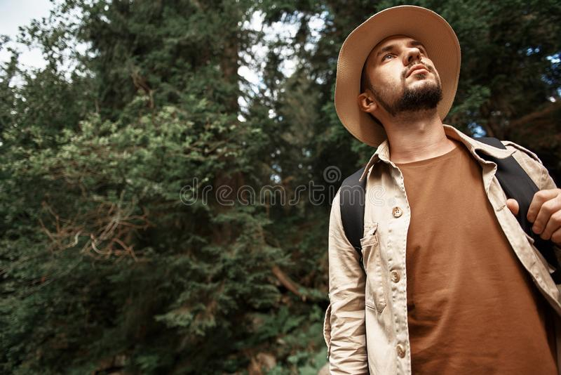 Calm traveler wearing big hat and thoughtfully looking into the distance royalty free stock image
