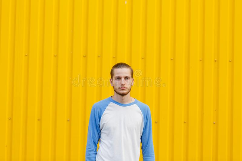 Calm, trendy man on a yellow background. Beautiful guy. Neutral expression concept. Copy space. stock photo