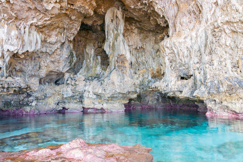 Calm turquoise colored water in pool in limestone cave on coast stock photos