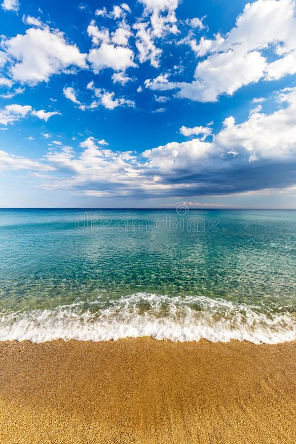 Calm turquoise sea. Calm turquoise sea and clouds on blue sky in Italy, Europe. Small waves on a sandy beach in the foreground royalty free stock images