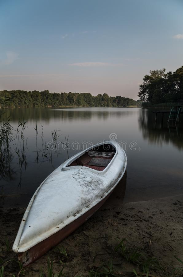 Calm water on lake with a white kayak. royalty free stock photos