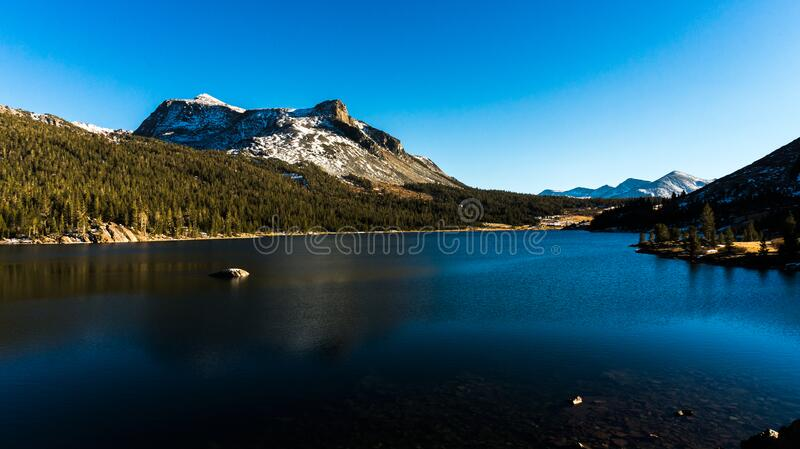 Calm Water Near Green Tress Under Snow-capped Mountain and Blue Sky royalty free stock image